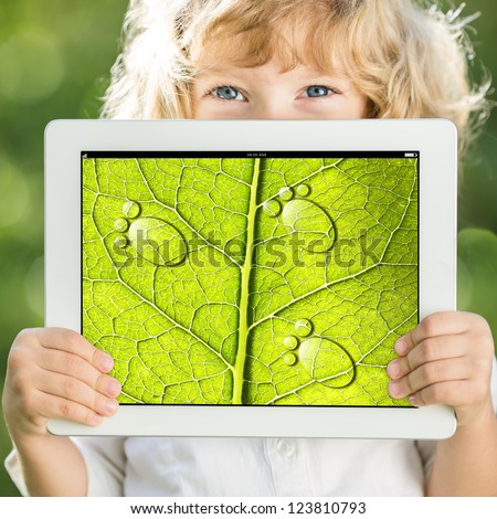 Happy child holding tablet PC with photo of green leaf texture outdoors in spring. Ecology concept - stock photo