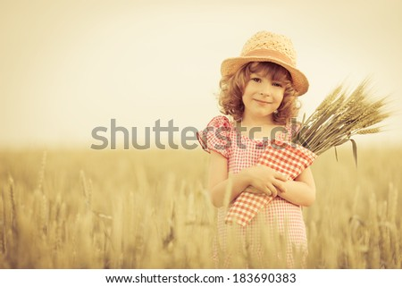 Happy child holding wheat in summer field - stock photo