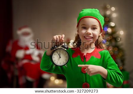 Happy child in Christmas elf costume with alarm. - stock photo