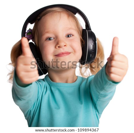 Happy child in headphones showing a thumb up - stock photo