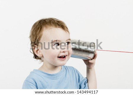 happy child in light grey background listening to tin can phone. horizontal image - stock photo