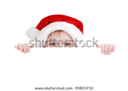 Happy child in Santa hat hiding face behind the blank board - stock photo