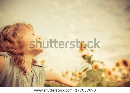 Happy child in sunflower field. Freedom concept - stock photo