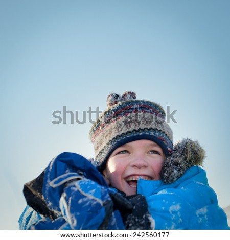 Happy child in winterwear laughing while playing in snowdrift outside - stock photo