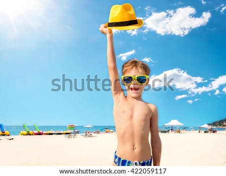 Happy child in yellow sunglasses on beach. Summer vacation concept   - stock photo