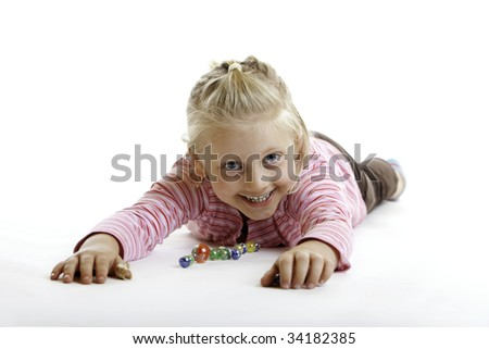 Happy Child is lying on the floor with marbles on white background - stock photo