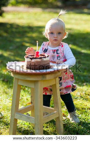 Happy child is outside in the park. She is looking at camera and celebrating the first year of  her birthday with cake. - stock photo