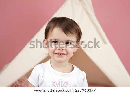 Happy child, kid, engaged in pretend play with teepee tent; laughing and smiling - stock photo