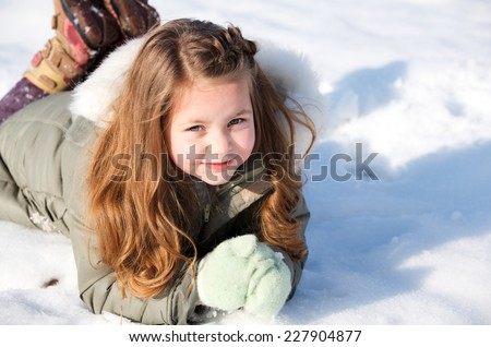 Happy child laying down in the snow - stock photo