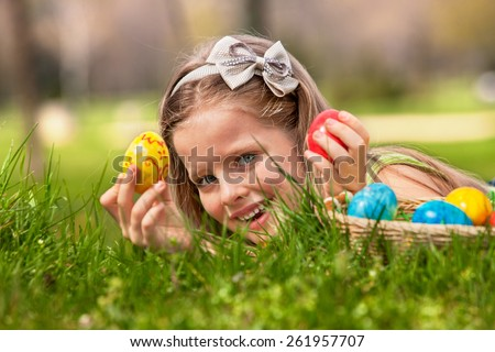 Happy child lying on green grass. and find easter egg outdoor.  - stock photo