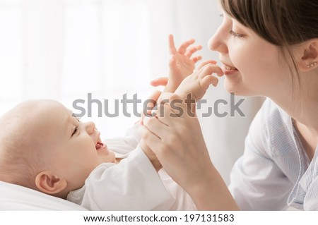 Happy child near to mum in the bed - stock photo