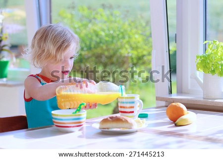 Happy child of preschool age, blonde curly toddler girl enjoying healthy breakfast eating sandwich and fruits and drinking orange juice sitting at bright sunny kitchen next to big garden view window - stock photo