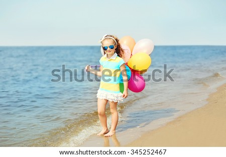 Happy child on summer beach playing with colorful balloons near sea - stock photo