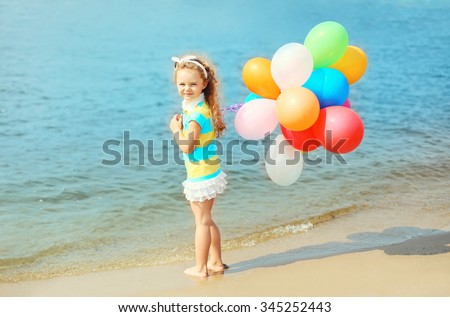 Happy child on summer beach with colorful balloons near sea - stock photo