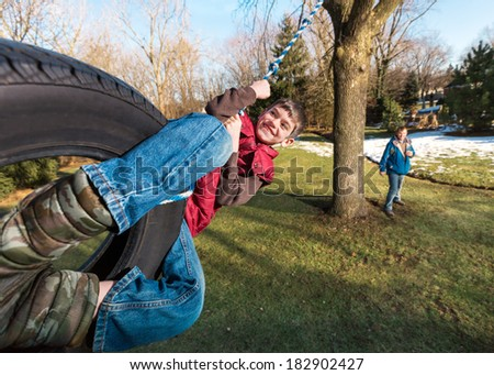 Happy Child on Tire Swing - stock photo