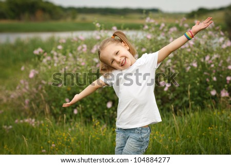 Happy child outdoors with outstretched arms - stock photo
