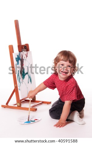 Happy child painting on easel - stock photo