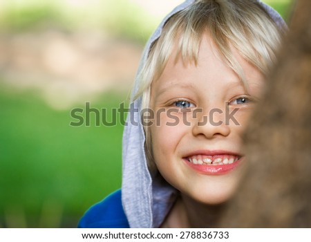 Happy child peeking from behind a tree with copy-space - stock photo