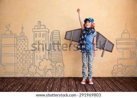 Happy child playing at home. Kid having fun with toy paper wings - stock photo