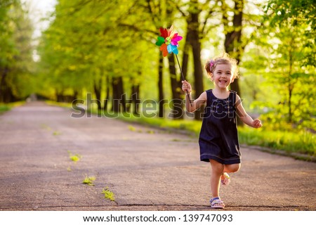 happy child playing in a spring garden - stock photo