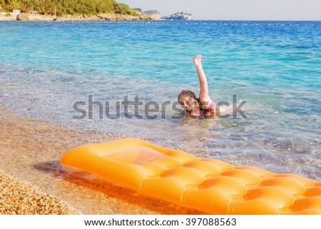 Happy child playing in blue water in the sea - stock photo