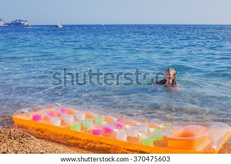 Happy child playing in blue water in the sea. Summer vacations concept - stock photo