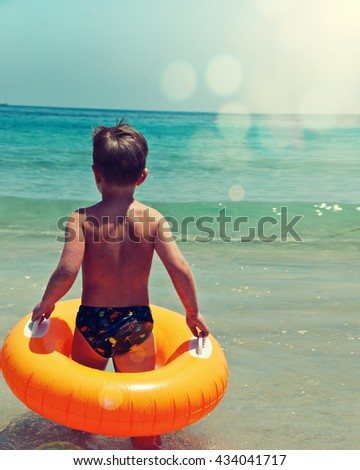 Happy child playing in blue water of sea - stock photo