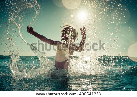 Happy child playing in the sea. Kid having fun outdoors. Summer vacation and healthy lifestyle concept. Toned image - stock photo