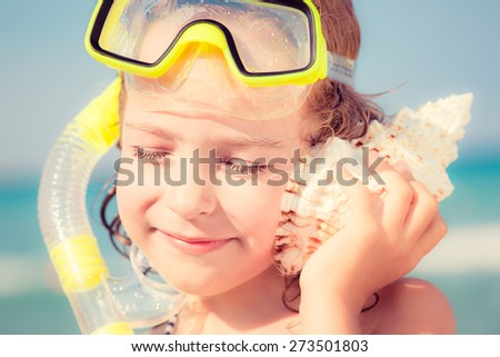 Happy child playing on the beach. Kid listen seashell. Summer vacations concept - stock photo