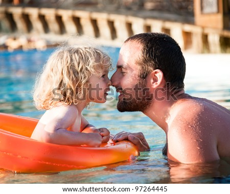 Happy child playing with father in blue water of swimming pool on a tropical resort at the sea. Summer vacations concept - stock photo