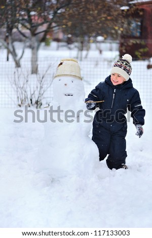 Happy child playing with snow and sculpts snowman. - stock photo