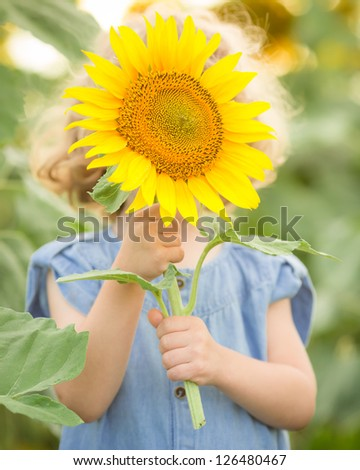 Happy child playing with sunflower in spring field - stock photo