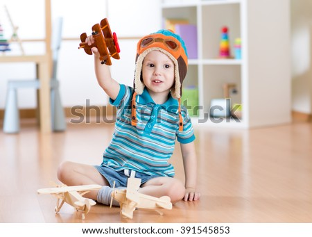 Happy child playing with toy airplane at home - stock photo