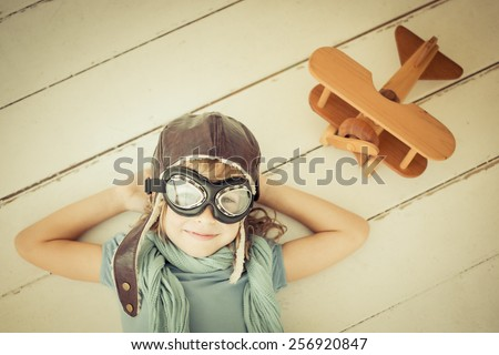 Happy child playing with toy airplane. Unusual high angle view portrait of kid on wood background. Retro toned - stock photo