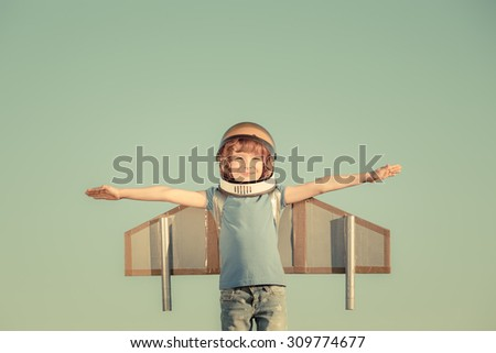Happy child playing with toy wings against summer sky background. Retro toned - stock photo
