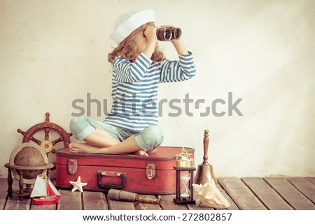 Happy child playing with vintage nautical things. Kid having fun at home. Summer sea dream and imagination. Adventure and travel concept. Retro toned image - stock photo
