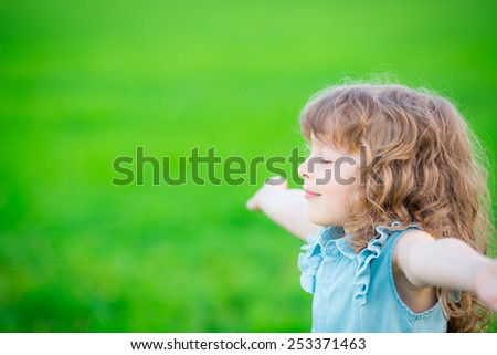 Happy child relaxing outdoors in spring filed - stock photo