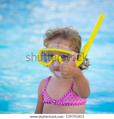 Happy child showing thumb up sign against swimming pool background. Summer vacations concept - stock photo