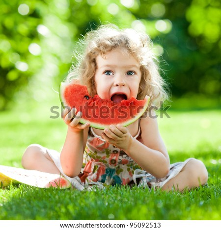 Happy child sitting on green grass and eating watermelon outdoors in spring park against natural sunny blurred background - stock photo