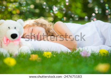 Happy child sleeping with toy teddy bear on green grass outdoors in spring garden - stock photo