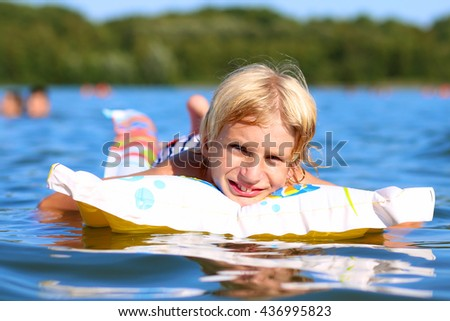 Happy child swimming in the lake. Healthy smiling school boy relaxing in the water on inflatable mattress. Active summer vacation concept. - stock photo