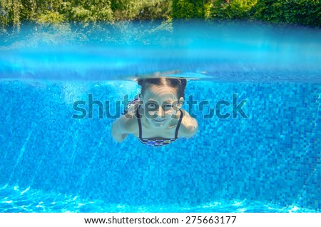 Happy child swims in pool underwater, active kid swimming, playing and having fun, children water sport  - stock photo
