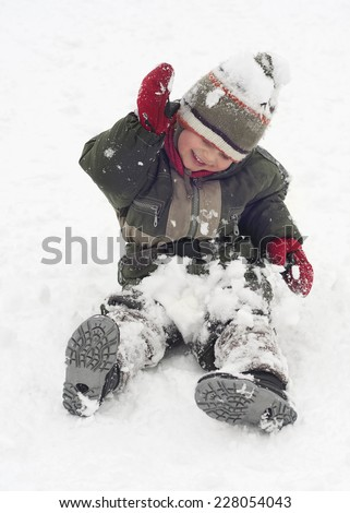Happy child toddler, boy or girl, sitting and playing in snow. - stock photo