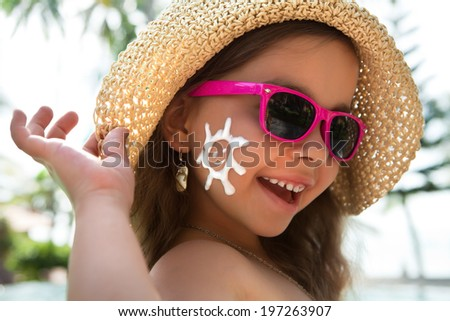Happy child wearing sunscreen on my face - stock photo