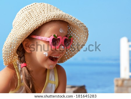 Happy child wearing sunscreen on my face against the sea - stock photo