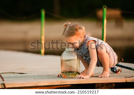 Happy child with a  fish he caught next to a pond - stock photo