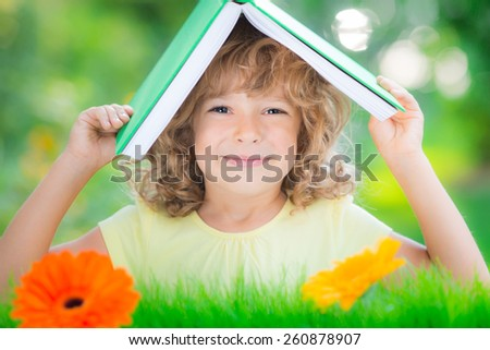 Happy child with book against green spring blurred background. Ecology concept - stock photo