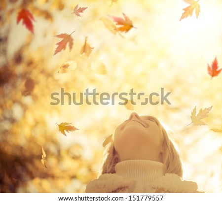 Happy child with maple leaves in autumn park against yellow blurred leaves background. Freedom concept - stock photo