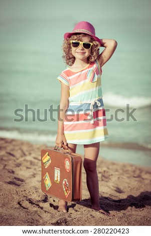 Happy child with vintage suitcase on the beach. Summer vacation and travel concept. Toned image - stock photo