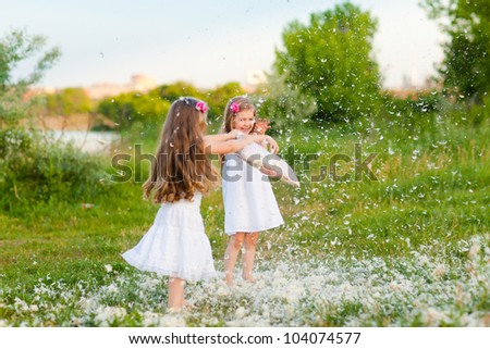 Happy childhood: Adorable little girls having fun with pillows outdoor - stock photo